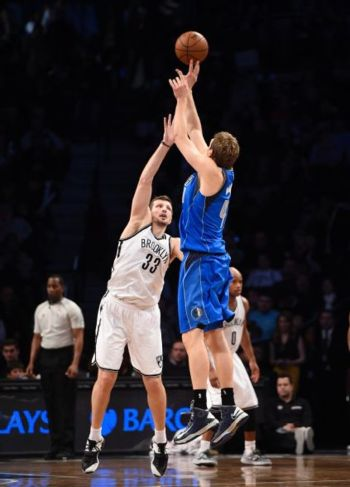 Dallas Mavericks forward Dirk Nowitzki (41) shoots a 3-point basket over Brooklyn Nets forward Mirza Teletovic (33) in overtime of an NBA basketball game Monday, Jan. 5, 2015, in New York. The Mavericks won 96-88. (AP Photo/Kathy Kmonicek)